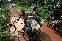 "Nande Toleca Bike Drivers--Resupply for Gold Mine--Early Warning System..From Paul Salopek:  ""To reach the land of the Mbutis - a 23,000-square-mile greenhouse called the Ituri Forest - you must follow men pushing squeaking bicycles.  This isn't difficult. You can see them swarming antlike throughout the wilds of eastern Congo. Jacknifed at the waist, generally emaciated, their eyes glazed with exhaustion, they manhandle bikes that are sagging under mountains of goods: bags of rice and gold dust, women's underwear and bullets, live goats and coffins, gasoline and cases of Coca-Cola. Some of these cargoes tilt and spill into the mud. Others bounce wildly down steep hills, and explode across jungle trails. No matter. Slowly, with stupefying patience, the cyclists stoop and gather up their battered merchandise; they plod onward, advancing at a shuffle, rolling their burdens across the colossal belly of a continent. .."