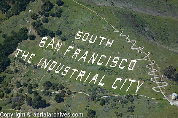 aerial photograph San Bruno Mountain, South San Francisco, San Mateo County, California.  Switchbacks are on the hiking trail passing the South San Francisco The Industrial City sign.
