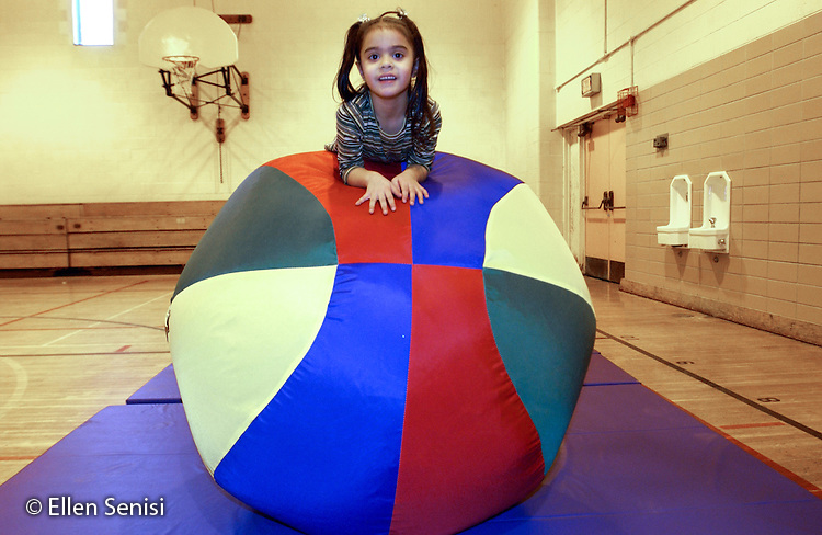 MR / Schenectady, NY                                  .Yates Arts-in-Education Magnet School (urban school).Pre-Kindergarten class; NYS Universal Pre-K Program.Girl (4, Puerto-Rican American) balances self on big ball on mat in gym class after being placed there by teacher..Val1.©Ellen B. Senisi