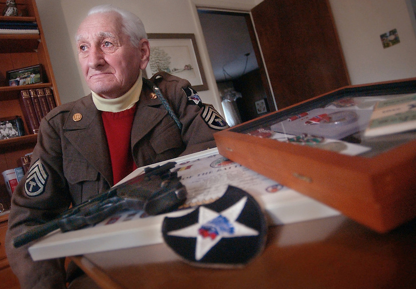 Lower Saucon Twp: Battle of The Bulge Army Medic  Julius Barkis, wearing his old army medic jacket, sits in from of some war memoribila in his home. in the forground is his Second Divison,know as the Texas and Oklahoma  diviosn. Also, reseting near some of his medals if a German P-38 Luger. ( CHUCK ZOVKO/TMC)..\ FOR DAVE VENDITTA WAR STORIES