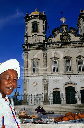 Bahia, Brazil. Street vendor selling Acaraje - fried bean flour and shrimp pattie in front of the Church of Nosso Senhor do Bonfim.