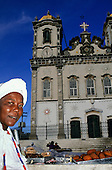 Bahia, Brazil. Street vendor selling Acaraje - fried bean flour and shrimp pattie in front of the Church of Nosso Senhor do Bonfim.