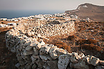 Roofs and doors of stone barns and walls overlooking Chora and the Assumption of the Virgin Mary church, Folegandros, Cyclades, Greece