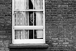 Old age pensioner looking through lace curtains, Whitechapel, east end London England 1975