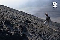 Pacific Ocean, Tanna island, Vanuatu, man climbing Yasur volcano in middle of lava bombs field (Licence this image exclusively with Getty: http://www.gettyimages.com/detail/sb10061763ai-001 )