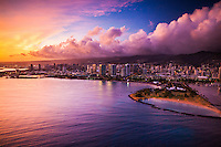 An aerial view at sunset of Magic Island and Ala Moana Beach Park (floating lanterns can be seen off of its shore) on O'ahu, with luxury condos and Ala Moana Shopping Center in the distance.