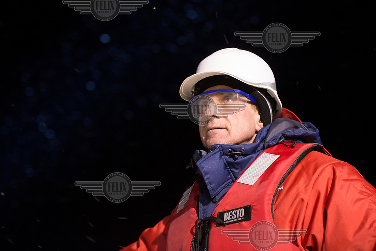 A member of deck crew on the icebreaker and supply ship the 'Fedor Ushakov' as it makes its way through the Barents Sea along the Northern Sea Route.