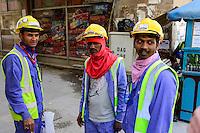 QATAR, Doha, Musheireb, construction boom for FIFA football world cup 2022 , the construction is done by migrant workers from all over the world, lunch time on the road / KATAR, Doha, Bauboom fuer die FIFA Fußball WM 2022/ KATAR, Doha, Bauboom fuer die FIFA Fußball WM 2022, Abrissviertel Musheireb, auf den Baustellen fuer Neubauten schuften Gastarbeiter aus aller Welt, Arbeiter bei Mittagspause auf der Strasse