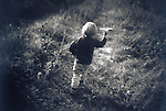 young boy walking in field with toy airplane