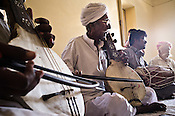 75-year-old Manganiyar artist, Saqar Khan (centre) plays Kamancha (music instrument) while his two sons, Ghewar Khan (45, Left on Kamancha) and Firoze Khan (38, right on Dholak) accompany him during field recordings inside their house in Hamira village of Jaiselmer district in Rajasthan, India. Photo: Sanjit Das/Panos