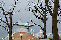 Italy. Lombardy region. Campione d'Italia. A raft, a tobbogan run and trees with no leaves. Winter scene on the lake. Campione d'Italia is occupying an enclave within the Swiss canton of Ticino, separated from the rest of Italy by Lake Lugano. Winter scene. 1.03.2008 © 2008 Didier Ruef