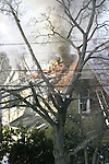 Firemen on ladder chopping into roof of  house on fire.