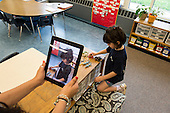 MR / Schenectady, NY. Zoller Elementary School (urban public school). Kindergarten classroom. Teacher uses iPad camera to photograph student (girl, 5) at play. Photographs in this classroom are used as an assessment tool for student's cognitive, emotional, and social growth throughout the schoolyear. MR: Coh2. ID: AM-gKw. © Ellen B. Senisi.