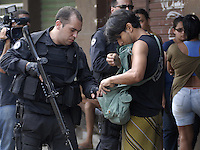 A policeman checks a suspect at Complexo da Penha, Rio de Janeiro, Brazil, November 25, 2010. Authorities in Rio de Janeiro try to control a fourth day of violence apparently orchestrated by drug gang members who have attacked police stations and burned cars in Rio de Janeiro city as protest by traffickers after being forced from their turf by police occupations of more than a dozen slums in the past two years..(Austral Foto/Renzo Gostoli)