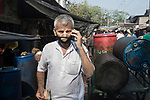 An owner of a business speaks on his mobile phone while his mask is not properly worn. India is going through a 21 days lock down for Corona virus pandemic. As the government gave relaxation to lockdown in the morning to shop for daily needs hence neither the social distancing is maitained nor people are using protective masks and gloves, now the authorities are concerned about the spread of the disease. Kolkata, West Bengal, India. Arindam Mukherjee.