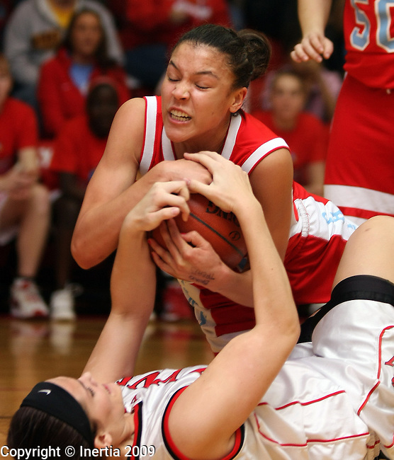BRANDON, SD - MARCH 2:  Carley Chambers #30 of Lincoln battles for a loose ball with Kate Swenson #54 of Brandon Valley in the first half of their game Monday night in the first round of their District 2AA game Monday night in Brandon. (Photo by Dave Eggen/Inertia)