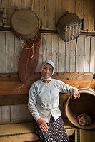 Japan, Mie Prefecture, Osatsu, Toba City. Third generation women Ama free diver, well into her 70's. Once pearl divers, they now collect seaweed, conch, lobster, shellfish. She runs a small Ama hut restuarant, Ama Hut Ozegosan, and cooks fresh seafood for guests. The white hood with the star is an Ama symbol and worn for good luck. Model released.