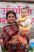 Kathmandu, Nepal.  Micro-credit Loan Recipient Poses in the Market with her Son.   Her Loan from the Non-Profit NGO CORE, Creating Opportunities and Resources for the Excluded, allows her to sell lettuce and other vegetables in the local market.  Both wear a tikka, or a bindi, a red mark between their eyebrows, a decorative mark of Hinduism traditionally said to protect against demons or bad luck.  The mother also wears a nose-ring and gold ear rings.