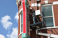 Chris Barth, a surveyor with Springfield Sign, takes measurements of the large soda fountain sign, Monday, September 13, 2021 above the Spark Cafe in Bentonville. Barth said they are replacing the sign. A spokesman with Walmart said he is conducting routine maintenance by replacing the lights. Check out nwaonline.com/210913Daily/ for today's photo gallery. <br /> (NWA Democrat-Gazette/Charlie Kaijo)