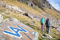 The Via Alta Verzasca is a five day ridge traverse hike above the Valle Verzasca in the Ticino region of Switzerland. Hikers passing a trail marker for the tour.