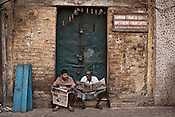 Street dwellers seen reading the newspaper early in the morning on the streets of Kolkata in West Bengal, India.