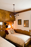 A bespoke built-in cupboard also works as a bedside table in this traditional mountain chalet