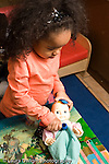 Education preschoool children ages 3-5 pretend play  3 year old girl using stethoscope on doll vertical
