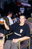 Belgrade, Yugoslavia. Young man sitting at a cafe table with beer glass smiling; Yugoslavia t-shirt.