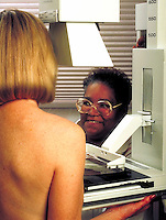 Radiology technician performs mammography test on female patient.