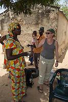Senegalese Woman Giving a Peace Corps Volunteer Two Boiled Eggs before she leaves on a trip.  Nixo Village, near Sokone, Senegal