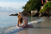 Yoga in the waves of Andaman sea - girl in pigeon pose practicing yoga at sunrise. Koh Lipe, Thailand