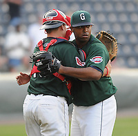 Catcher Christian Vazquez (15) of the Greenville Drive hugs pitcher Dennis Neuman after the final pitch in a game against the Augusta GreenJackets on April 10, 2011, at Fluor Field at the West End in Greenville, South Carolina. (Tom Priddy / Four Seam Images)