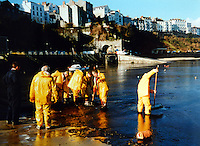 Pictured: Workers cleaning up the oil spill from Tenby beach in Pembrokeshire, west Wales<br /> Re: The Sea Empress oil spill occurred at the entrance to the Milford Haven Waterway in Pembrokeshire, Wales on 15th February 1996 which was followed up by a clean up operation has begun