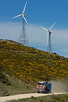 Wind turbines on hill above dirt road with truck, Tarifa, Andalusia, Spain.