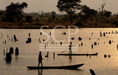 Chisimba, Zambia. Two boys punting canoes on a dammed lake with the stumps of drowned trees. Northern Province.