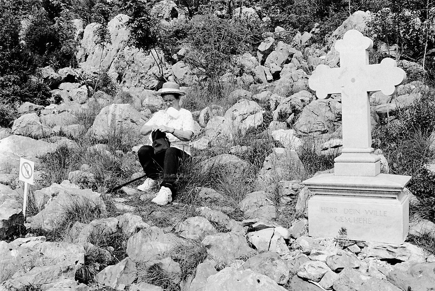 Bosnia. Medjugorje. Podbrdo, also called the Apparition Hill, is the place above the village of Bijakovici near Medjugorje where the six visonaries in the first days saw the Virgin Mary. Since then it is here that the pilgrims gather for prayer of the rosary. A sign prohibits to light any candles to avoid  a risk of fire on the hill. © 2002 Didier Ruef