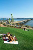 Summer Recreational Activities at White Rock, BC, British Columbia, Canada - People sunbathing at White Rock Pier along Seaside Promenade Walkway and Semiahmoo Bay