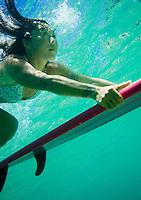 A local Asian woman duck dives a wave at Waimea Bay