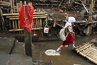 A young girl jumps onto a river raft in a slum community in central Jakarta.<br />