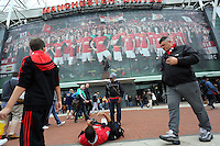 Pictured: A man lies on the ground to take a picture of his friend outside the Old Trafford. Saturday 16 August 2014<br />