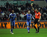Pictured: Ashley Cole of Chelsea (L) sees his first yellow card by referee A Marriner. Tuesday, 31 January 2012<br /> Re: Premier League football Swansea City FC v Chelsea FCl at the Liberty Stadium, south Wales.