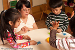 Preschool Headstart 3-5 year olds female teacher working with group of children playing game popping counters into a bowl one boy olding up four fingers horizontal