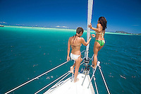Young girls in bikinis on the bow of a sailboat in Kaneohe Bay, Oahu, Hawaii