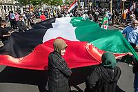 """Etwa 400-500 Menschen demonstrierten am Samstag den 1. Juni 2019 in Berlin mit dem sog. """"Al Quds-Marsch"""" gegen Israel. Alljaehrlich marschieren radikale Islamisten, Anhaenger der Hisbollah und der Diktatur im Iran zum Ende des islamischen Fastenmonats Ramadan durch Berlin und rufen zum Kampf gegen Israel auf. Sie wollen """"die Juden"""" aus Jerusalem (Quds) vetreiben und wollen Israel vernichten. Der """"Quds-Tag"""" wurde 1979 vom iranischen Revolutionsfuehrer Ayatollah Khomeini als politischer Kampftag etabliert, an dem weltweit fuer die Vernichtung Israels geworben wird.<br /> Dagegen protestierten fast 1.000 Menschen. Sie demonstrieren für Solidaritaet mit Israel und protestieren gegen jede Form von antisemitischer und islamistischer Propaganda in Berlin und forderten ein Verbot des Aufmarsches.<br /> Im Bild: Demonstranten mit einem ueberdimensionalen Palaestina-Flagge.<br /> 1.6.2019, Berlin<br /> Copyright: Christian-Ditsch.de<br /> [Inhaltsveraendernde Manipulation des Fotos nur nach ausdruecklicher Genehmigung des Fotografen. Vereinbarungen ueber Abtretung von Persoenlichkeitsrechten/Model Release der abgebildeten Person/Personen liegen nicht vor. NO MODEL RELEASE! Nur fuer Redaktionelle Zwecke. Don't publish without copyright Christian-Ditsch.de, Veroeffentlichung nur mit Fotografennennung, sowie gegen Honorar, MwSt. und Beleg. Konto: I N G - D i B a, IBAN DE58500105175400192269, BIC INGDDEFFXXX, Kontakt: post@christian-ditsch.de<br /> Bei der Bearbeitung der Dateiinformationen darf die Urheberkennzeichnung in den EXIF- und  IPTC-Daten nicht entfernt werden, diese sind in digitalen Medien nach §95c UrhG rechtlich geschuetzt. Der Urhebervermerk wird gemaess §13 UrhG verlangt.]"""