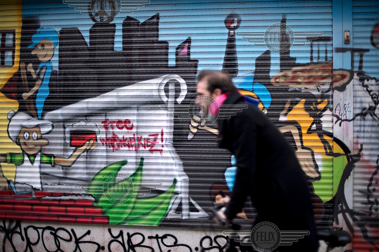 A man rides his bicycle along Wrangelstrasse, past graffiti covered walls in Kreuzberg, a district undergoing significant redevelopment and gentrification.