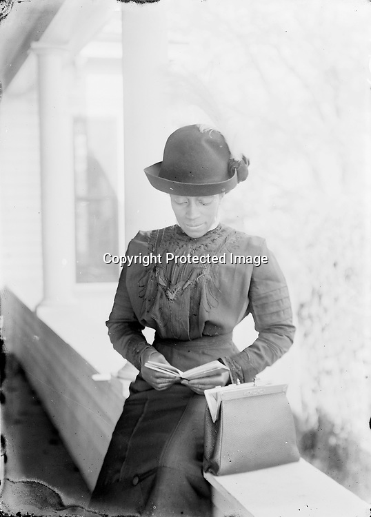 Young Woman with Book.<br /> A number of the photographs feature people with books, a testament to how strongly education was stressed in Lincoln's African American community. Here, an elegantly attired young woman reads a small book. Johnson composed several photographs in the well-lit shade of this big porch, which may have been at the house of William Cotton, a letter carrier who lived near Johnson and who worked from the Post Office where the photographer was a janitor.<br /> <br /> Photographs taken on black and white glass negatives by African American photographer(s) John Johnson and Earl McWilliams from 1910 to 1925 in Lincoln, Nebraska. Douglas Keister has 280 5x7 glass negatives taken by these photographers. Larger scans available on request.