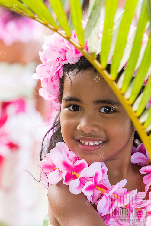 A girl wearing a pink plumeria lei and haku head lei poses with a palm frond before a hula performance in Halei'wa, North Shore, O'ahu.