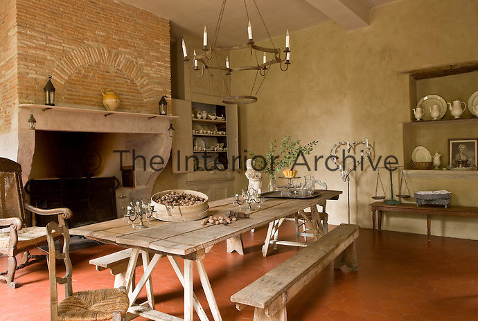 An impressive 17th century brick and stone fireplace dominates the kitchen which is furnished with a rustic trestle table made up of four lengths of planking and flanked by a pair of rustic farm benches