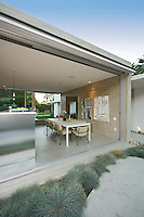 View from outside into a mid-century modern dining room and kitchen with movable aluminum walls Stock photo of residential dining room