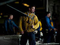 120315-N-DR144-434 ARABIAN SEA (March 15, 2012) Aviation Boatswain's Mate (Handling) 3rd Class Joshua Mee, assigned to the Air Department's V-3 Division, directs an aircraft move in the hangar bay aboard the Nimitz-class aircraft carrier USS Carl Vinson (CVN 70). Carl Vinson and Carrier Air Wing (CVW) 17 are deployed to the U.S. 5th Fleet area of responsibility.  (U.S. Navy photo by Mass Communication Specialist 2nd Class James R. Evans/Released)
